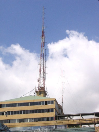 Four FM transmitting antenna arrays on two stayed masts on the roof of a commercial building